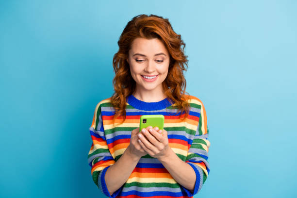 Photo of wavy hairdo person hands hold device write sms wear pullover isolated on blue color background stock photo