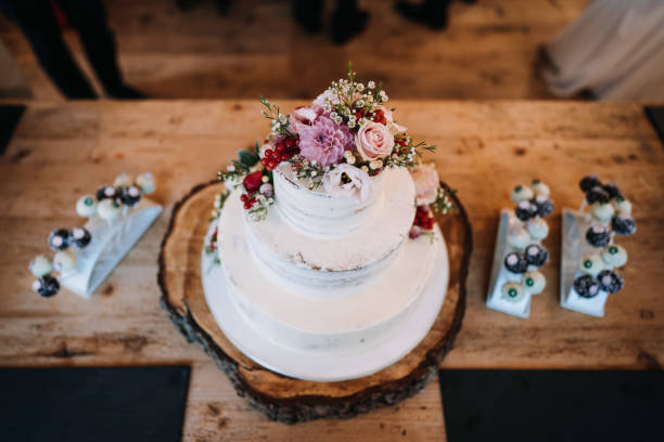 photo of wedding cake with flowers on a table stock photo