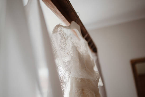 photo of wedding dress hanged on a bed stock photo
