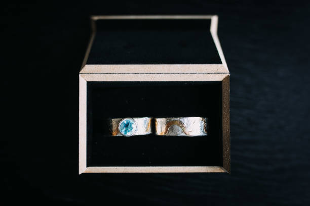 photo of wedding rings in a box with black background stock photo