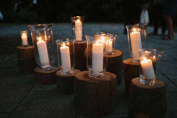 photo of white candles in glass on wood stock photo