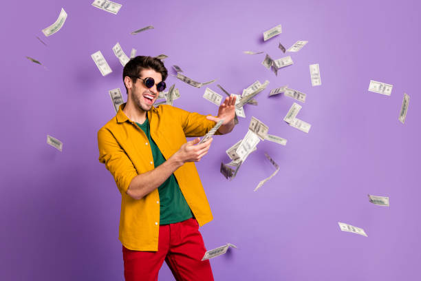 photo of white cheerful brown haired trendy casual man with bristle throwing cash with crazy emotions on face in red pants yellow shirt isolated violet pastel color background - throw money away stock pictures, royalty-free photos & images