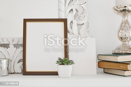 1129542015 istock photo Photo of white horizontal interior with white book shelf with old empty frame. Decor for mockup 1128166848