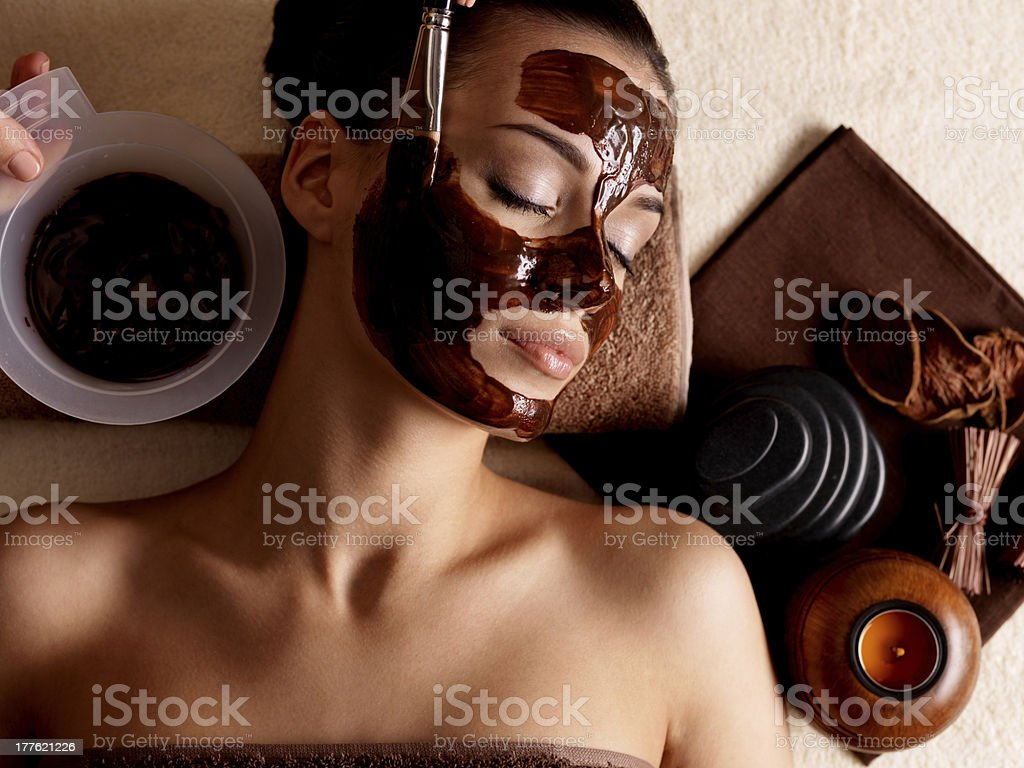 Photo of woman at a spa wearing a mud mask and relaxing stock photo