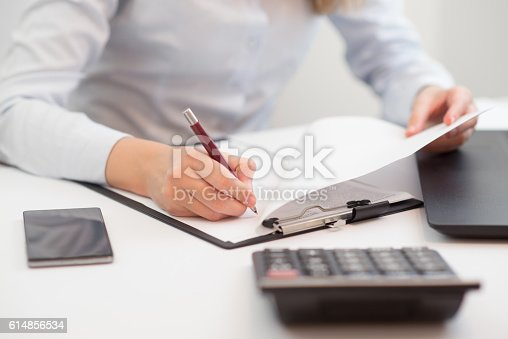 istock Photo of Woman doing her home finances 614856534