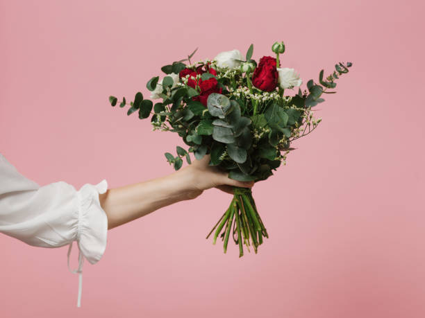 photo de femme tenant beau bouquet de fleurs roses fond rose - bouquet de fleurs photos et images de collection