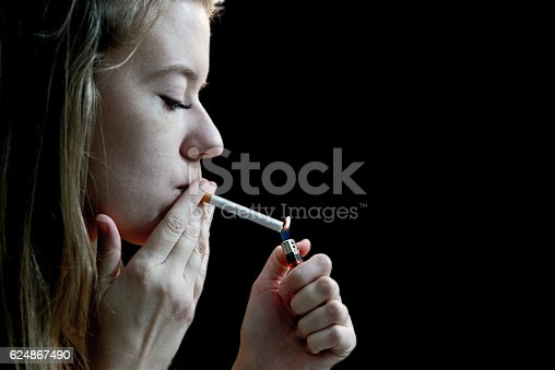 Photo of woman lighting a cigarette against a black background
