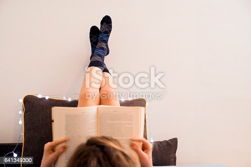 501914364istockphoto Photo of Woman lying in bed while reading a book 641349300