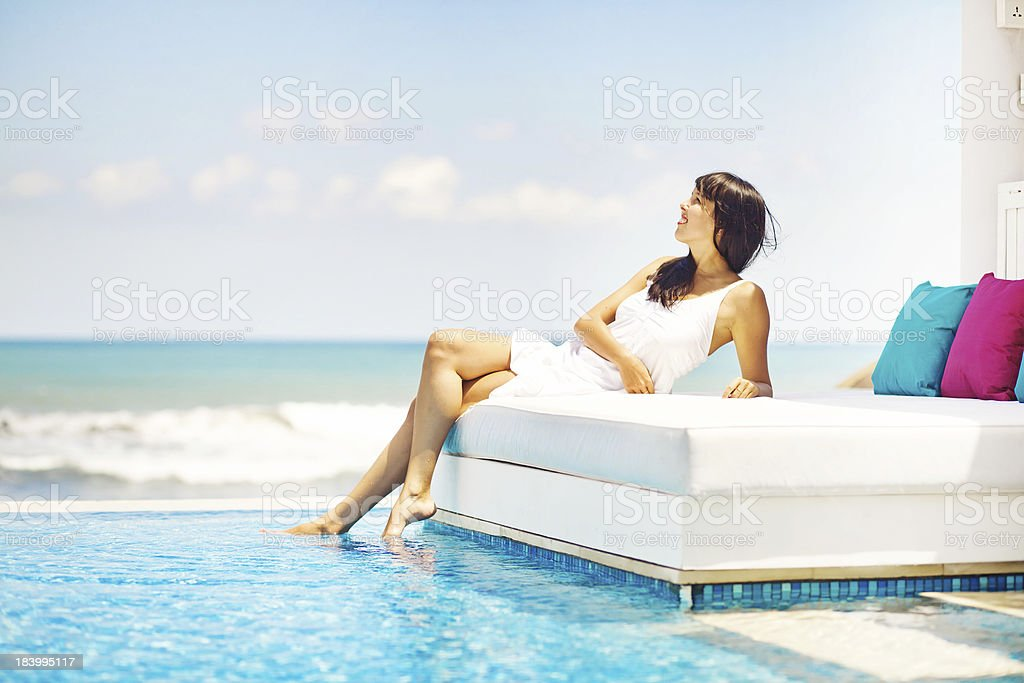 Photo of woman on sun bed dipping toes in water stock photo
