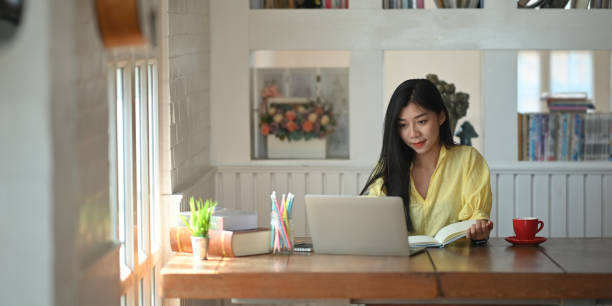 Photo of woman sitting and taking note while sitting in front her computer laptop that putting on wooden working desk and surrounded by coffee cup, pencil holder, potted plant and stack of books stock photo