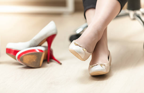 photo of woman wearing ballet flats instead of high heels - flat shoe stock photos and pictures
