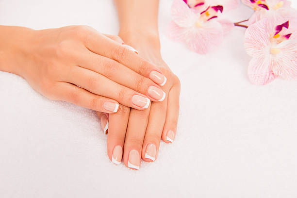 photo of woman's hand with manicure and flower of orchid stock photo