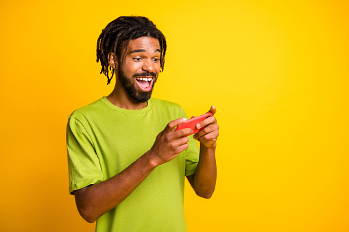 Photo of young afro man hold smartphone happy excited play video games wear green t-shirt isolated over yellow color background