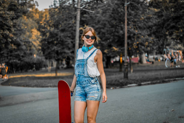 photo of young attractive beautiful and fashion young woman posing with a skateboard. she is standing and enjoying in the city street during a spring day. happy and casually dressed woman is taking a break during sunset outdoors.beautiful young woman with - spring fashion stock pictures, royalty-free photos & images