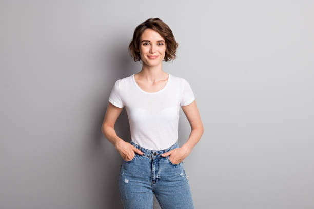 Photo of young attractive cheerful girl wear casual outfit hands in pocket confident smile isolated over grey color background stock photo