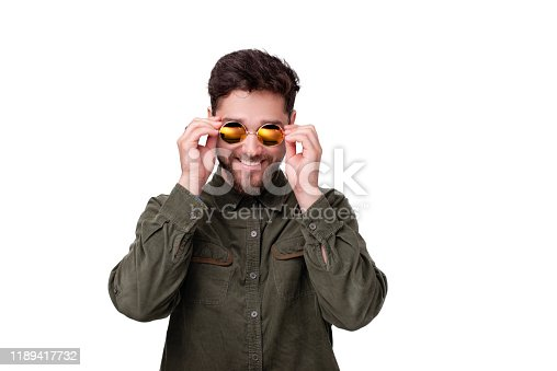 951331990 istock photo Photo of young bearded guy touching frame of sunglasses, over white background 1189417732