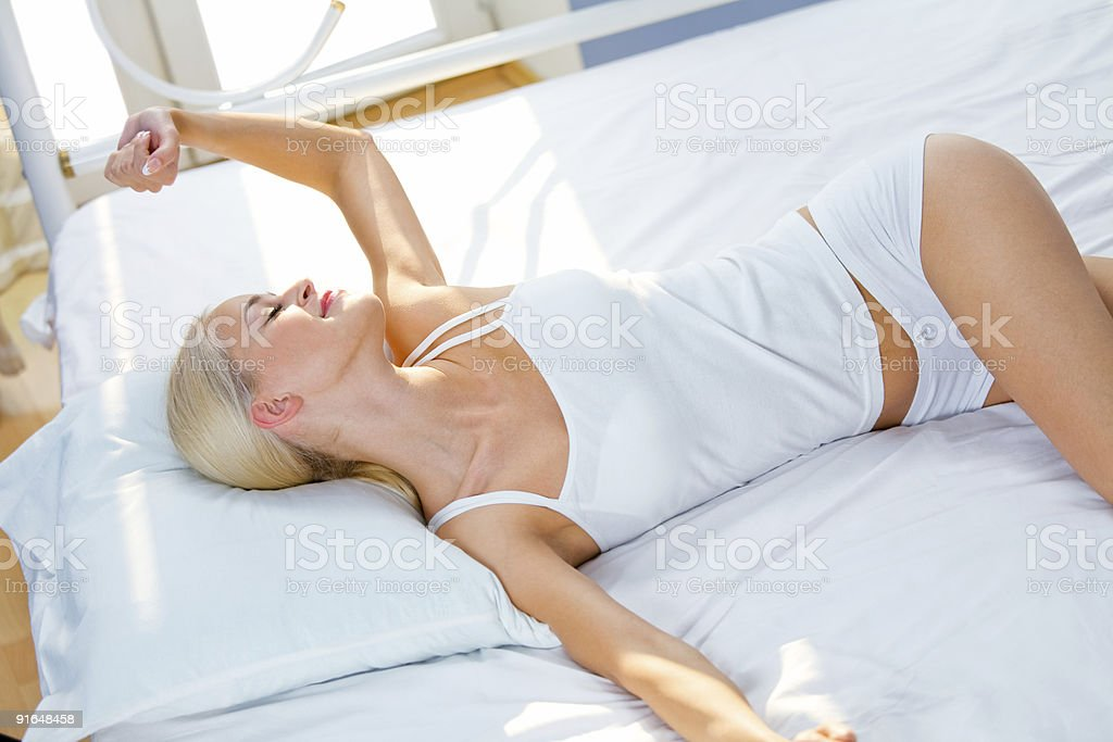 Photo of young beautiful woman on bed at bedroom royalty-free stock photo