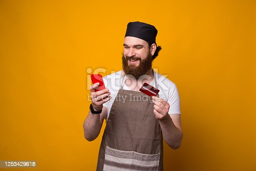 istock Photo of young Chef man using smartphone and credit card for online banking 1253429618