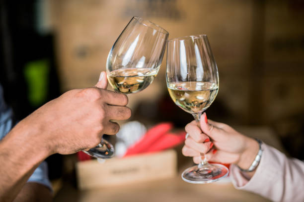 Photo of young couple cheering with wine Photo of young couple cheering with wine. Close up. white wine stock pictures, royalty-free photos & images