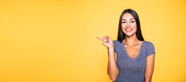 photo of young excited beautiful happy brunette woman, girl pointing away and smile isolated on yellow background banner - finger point stock photos and pictures