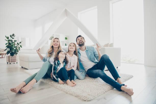 Foto de la familia joven adoptó dos niños mover nuevos apartamentos tienen manos techo de papel con la esperanza de mejor futuro - foto de stock