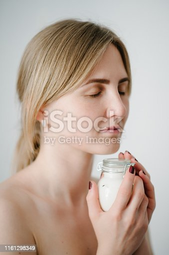 532331272 istock photo Photo of young girl with flawless skin. Smiling woman holding little jar of skin cream and applying bottles lotion, natural cosmetics. Cosmetology, beauty and spa. Wellness. Close up. 1161298349