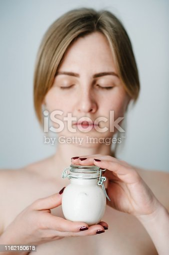 532331272 istock photo Photo of young girl with flawless skin, woman holding in hands little jar of skin cream or bottles lotion, natural cosmetics. Cosmetology, beauty and spa. Wellness. Close up. selected focus. 1162150618