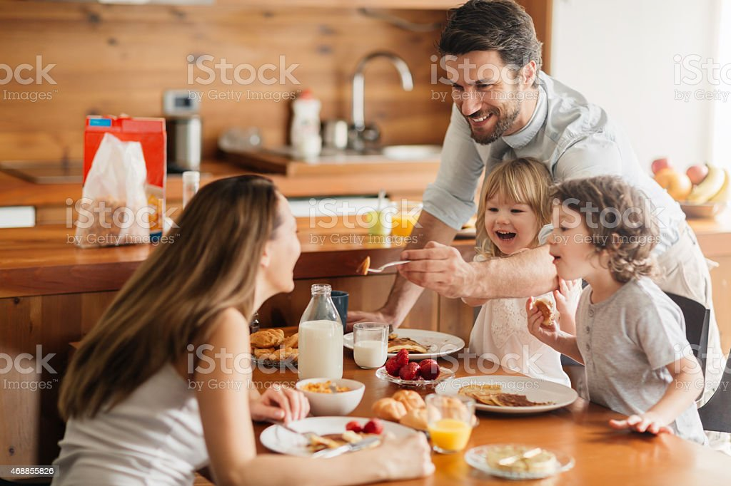 Photo of young happy family having their breakfast stock photo