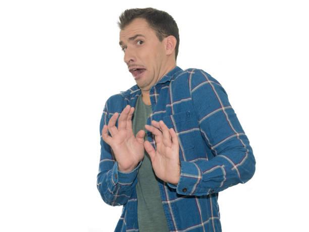 Foto do homem novo, receoso e aterrorizado com gesto do batente da expressão do medo com mãos. Conceito do pânico - foto de acervo