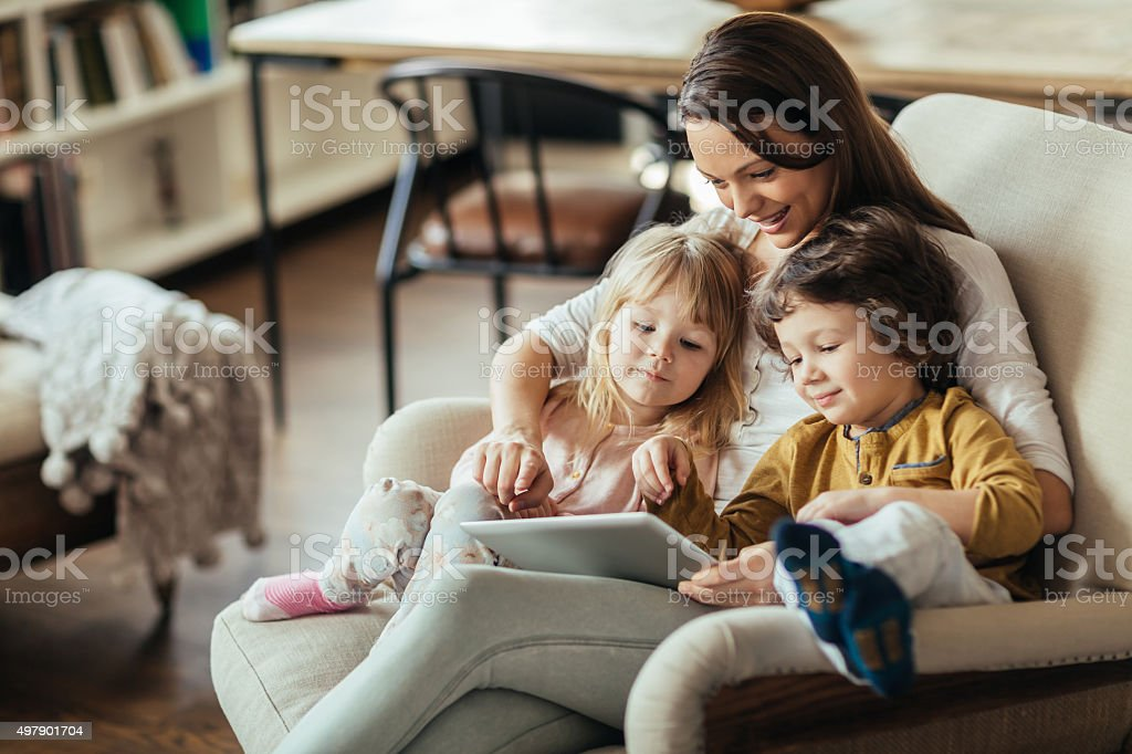 Photo of young mother and children sitting with tablet stock photo
