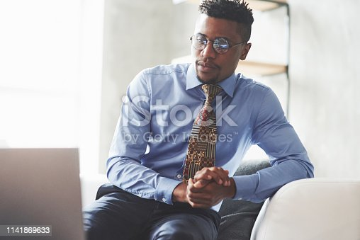 530281733istockphoto Photo of young stylish black man in the suit and glasses sitting on the sofa and looking at a laptop 1141869633