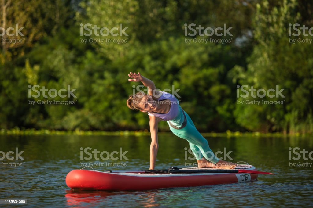 Photo of young woman doing hand stand on stand up paddle board. She...