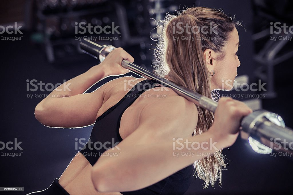 Photo of young woman with barbell flexing muscles in gym stock photo