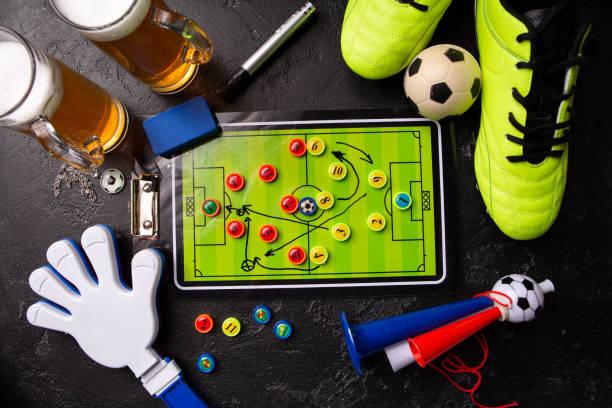 Foto auf zwei Tassen Schaumbier, Tischfußball, Ball, Fußballschuhe, Pfeife, Rasselspielzeug – Foto