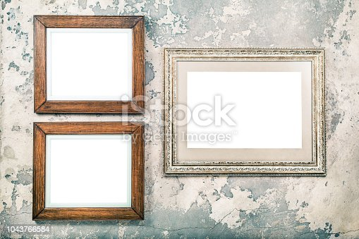 istock Photo or picture frame blank hanging on vintage aged grunge textured concrete wall background. Retro old style filtered photo 1043766584