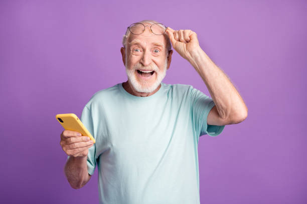 Photo portrait of elderly man lifting up glasses holding phone in one hand isolated on vivid purple colored background stock photo