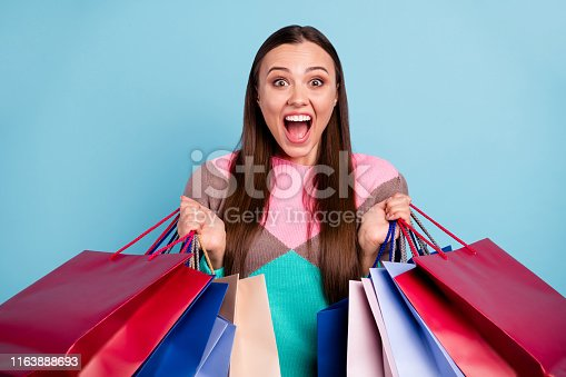 istock Photo portrait of excited cheerful positive glad nice optimistic girl holding many full bags in hands isolated bright background 1163888693