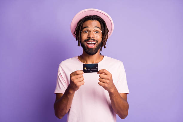 Photo portrait of excited guy holding credit card in two hands isolated on vivid violet colored background stock photo