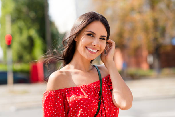 Photo portrait of happy adorable brunette enjoying sunny day on the street in summer weather with wind stock photo
