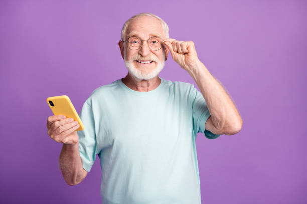 Photo portrait of happy man touching glasses holding phone in one hand isolated on vivid violet colored background stock photo