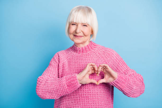 Photo portrait of happy old woman showing heart with fingers on chest isolated on pastel blue colored background stock photo