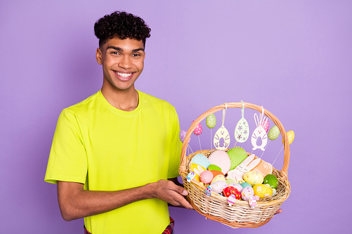 Photo portrait of young curly guy keeping easter corb colorful eggs sweets celebrating holiday isolated on pastel purple color background