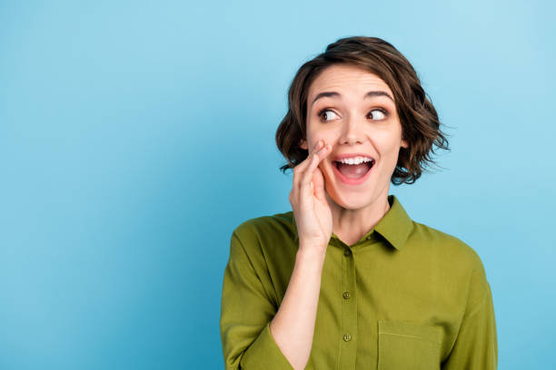 Photo portrait of young pretty girl with short hair telling secret information rumouring gossiping wearing green shirt isolated on blue color background stock photo