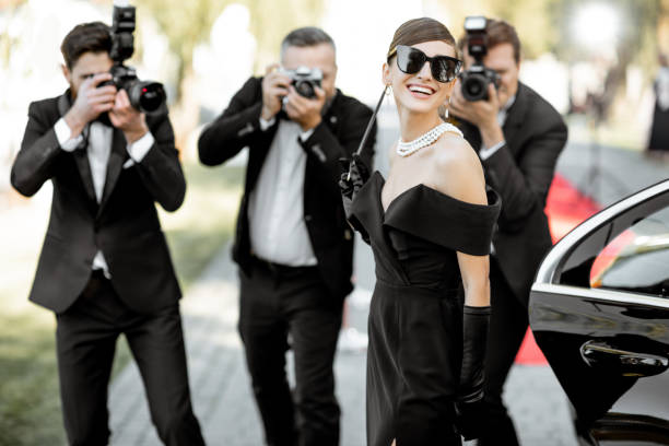 Photo reporters photographing actress ariving on the awards ceremony Beautiful woman dressed in retro style as a famous movie actress arriving on the awards ceremony with photo reporters taking pictures of her fame stock pictures, royalty-free photos & images