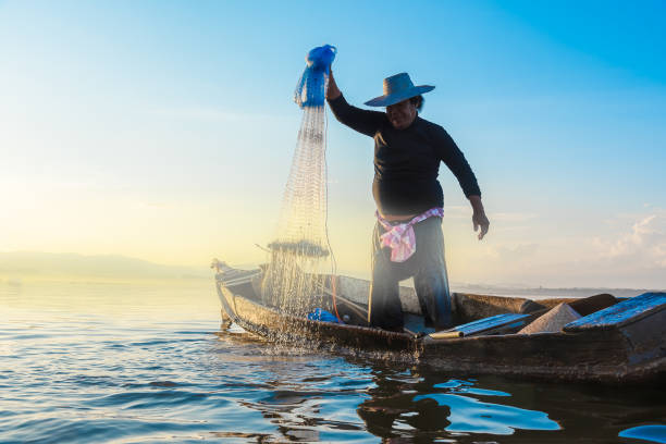 photo shot of water spatter from fisherman while throwing fishing net on the lake. silhouette of fisherman with fishing net in morning sunshine. stop motion water drop. - stop motion stock photos and pictures