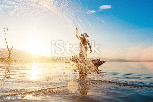 Photo shot of water spatter from fisherman while throwing fishing net on the lake. Silhouette of fisherman with fishing net in morning sunshine.