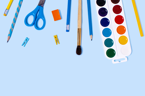 School supplies on blue background. Back to school flat lay picture.