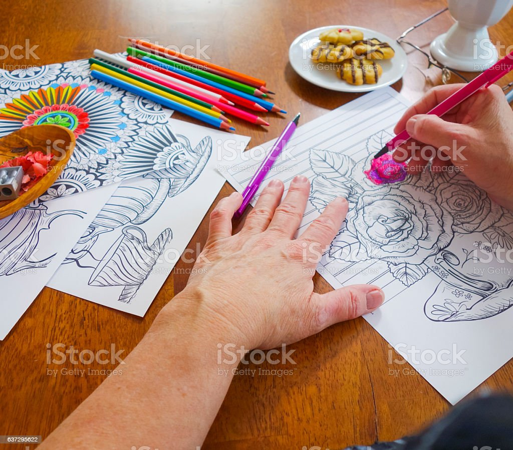 POV photo Woman's Right Hand Holding Pink Marker Coloring Flowers stock photo