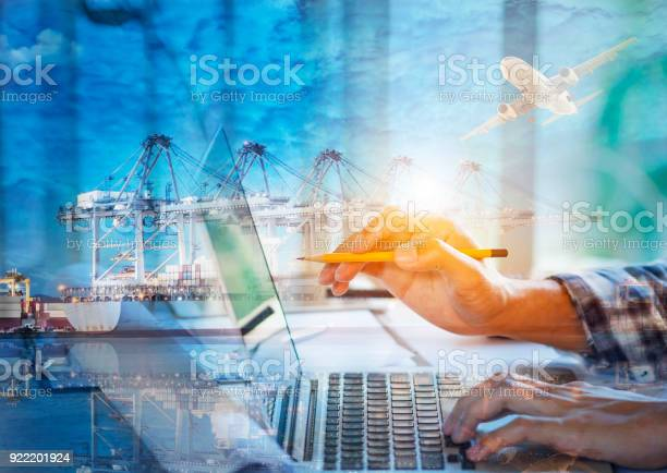Photo Young Account Managers Crew Working With New Startup Project Notebook On Wood Table Double Exposure Photo Of Containers Loading By Crane At Sunset Stock Photo - Download Image Now