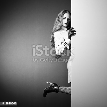 istock Photo young beautiful woman in a raincoat in interior 949999666